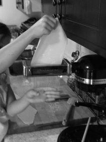 Cutting spaghetti noodles with KitchenAid pasta machine black and white photo on andreabadgley.com